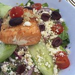 Huge piece of perfectly grilled salmon atop Greek salad loaded with ingredients. Expensive but y