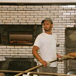 An expert pizza maker looking intrigued by the camera. Behind him is the huge coal fired oven.