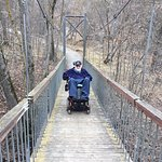 Me in my wheelchair traversing a bridge across a gorge.
