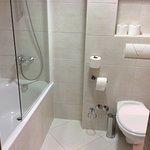 Badezimmer mit Badewanne, WC und Waschbecken mit möglichen Blick in den Schlafbereich
