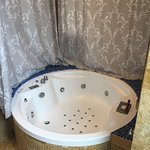 Whirlpool bath. Behind the curtain is a window through which you can see the tv in the seating a