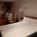 Sofá-cama abierto en el espacio inferior de la Junior Suite Dúplex, sillón, mesa de comedor y si