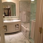 lovely bathroom with deep tub and glass shower and sink. Separate toilet.
