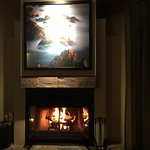 Fireplace roaring and a great picture lighted above