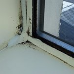 Black mould around windows, sealant badly applied to cover up.