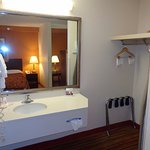 vanity sink and mirror, hair dryer, suitcase stand, hangers, ironing board, and safe area