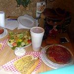spaghetti, garlic bread, and salad with iced tea