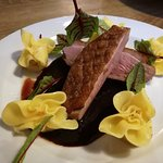 Duck breast on a blackcurrant sauce with dumplings stuffed with pear and taleggio cheese.