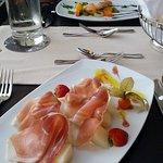 Melone mit Schinken und Garnelenspieß auf mediterranem Gemüse