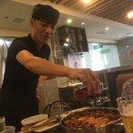 Waiter adding fresh cilantro to simmering pan