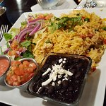 Yellow rice with chicken, beef and pork. Sides dish of black beans and salad.