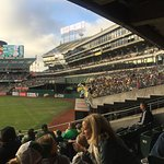 The oakland fans in bleachers cheer on the A's