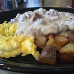Sausage gravy over biscuits with scrambled egg & home fries.