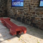 Guns exhibit pieces and bench outside Art Center