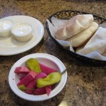Pickled turnips and peppers along with pitas and sauces free appetizer