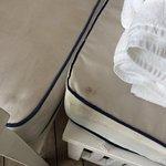 Abnutzung an der Wand, sowie Flecken auf dem Sessel.