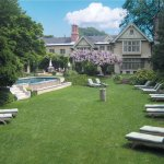 The Baker House back gardens with infinity-edge pool, teak chaise lounges and 200 year old wiste