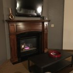 Working gas fireplace, wall-mounted TV, big couch with coffee table