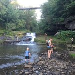 Families exploring the Cascade Falls of the South Fork of the Kinni with the Swinging Bridge abo