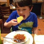 Enjoying the child's-size spaghetti bolognese and garlic bread