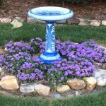 Walk around back and you will see this adorable bird bath and an antique bath tub full of flower