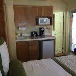 queen bed, kitchenette, door to bath