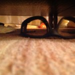 The view of under the bed with the discarded sunglasses, used tissue and socks.