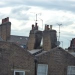 View from bedroom window of unusual inclined chimney stacks.