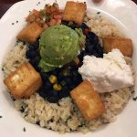 "Black beans and brown rice bowl with tofu, guacamole, and vegan ""sour cream."""