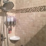 Beautiful Shower with a hand held or a rain shower head. Soap, shampoo and conditioner on the wa
