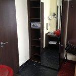 Blick vom Waschbecken zum Kleiderschrank mit Safe. Links Tür zum Bad.
