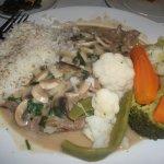 Steak with mushroom sauce, rice and vegetables.