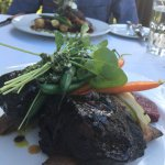 delicious beef short ribs and delicious pork chop in background both with seasonal vegetables