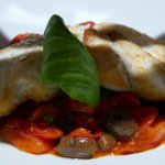 Lake fish on pomodoro with basil, olives, capers