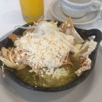 A pot of Chilaquiles (tortilla chips with chicken, grated cheese and green tomato sauce)