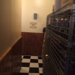 dingy hall to bathrooms with cleaning supplies in metal racks