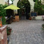Through the gate is a beautiful court yard with a water fountain and rustic cafe tables.