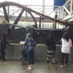 Huge iron wheel powered by giant piston form wood burnng steam engine