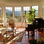 The common living room is shown with piano, telescope and tasteful decor.