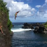 Cliff jumping into a beautiful deep pool in a cove past Hana