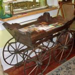 Entry way with a quaint antique buggy holding brochures.