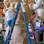 2 workers adding paper mache to the styrofoam figure.