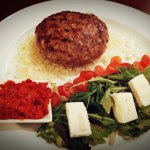 Minced beef pattie with cheese and prosciutto, with feta cheese salad and harissa paste