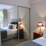 Queen size bed with huge wardrobe, bedside tables with reading lamps on both sides.