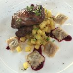 Duck with fois gras ravioli with cooked apple and plum sauce.