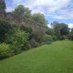 Well mainted peaceful gardens with castle wall backdrop