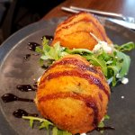 Deep fried, breaded mash potatoes over green salad with goat cheese and balsamic drizzle