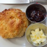 a peach scone with raspberry jam and butter