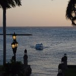 The boat shuttle coming in from the private island at sunset. View from pool at Renaissance Mari
