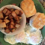 Eggs over-easy with cottage fried potatoes, bacon and biscuits.